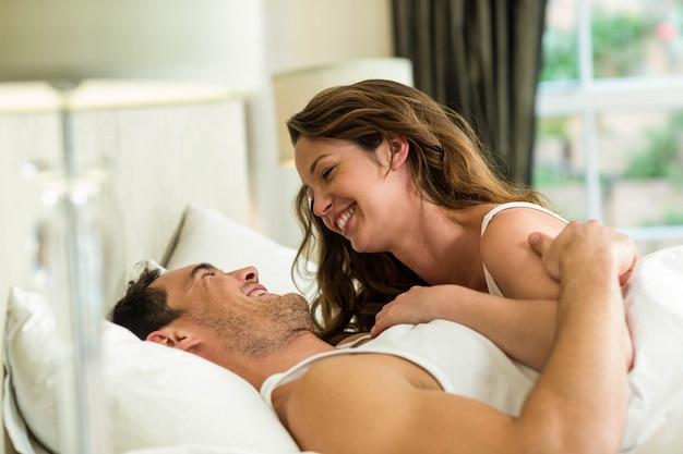 Pareja romántica abrazando en la cama en el dormitorio Foto Premium