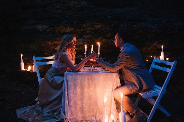 Pareja romántica cogidos de la mano juntos a la luz de las velas durante r Foto Premium
