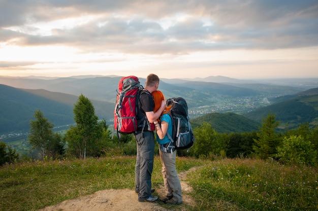 Pareja romántica excursionistas con mochilas de pie abrazando y disfrutando de la vista del hermoso mirador abierto en las montañas, bosques, colinas, pueblo en el valle y cielo nublado Foto Premium