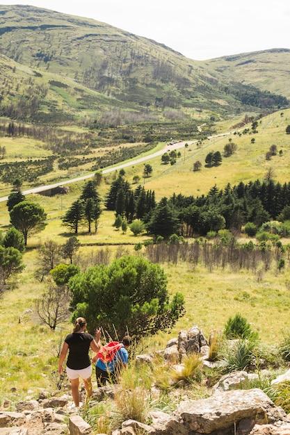 Pareja de senderismo en la colina de piedra cerca del valle Foto gratis