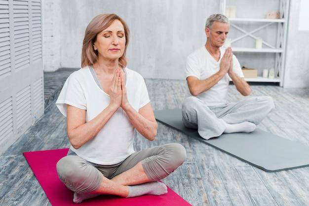 Pareja senior concentrada realizando yoga en casa Foto gratis