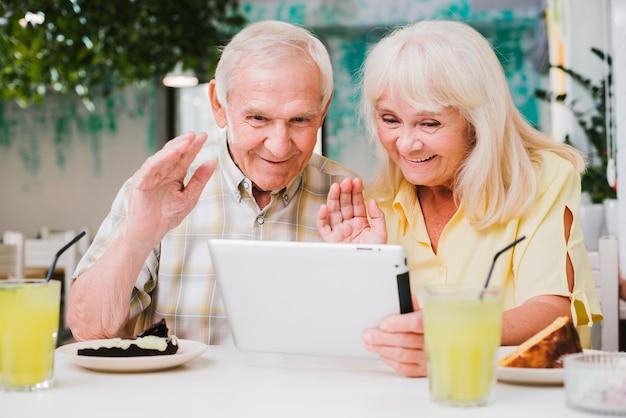 Pareja senior positiva en café con videollamada en tableta Foto gratis