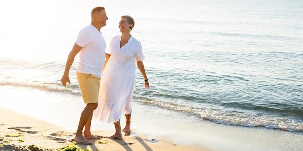 Pareja senior de tiro completo divirtiéndose en la playa Foto gratis