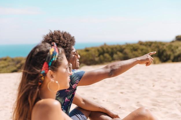 Pareja sentada en la playa y chico mostrando algo lejos a chica Foto gratis