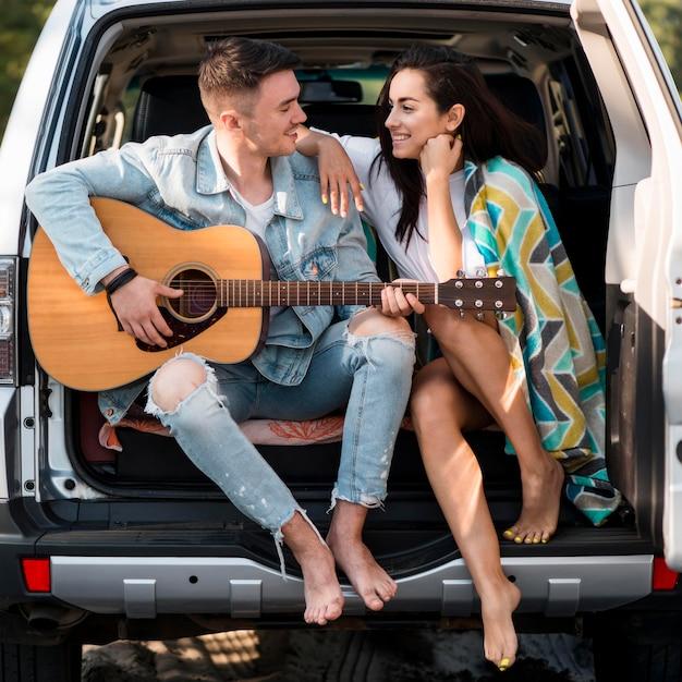 Pareja, sentado, en, baúl, con, guitarra Foto gratis