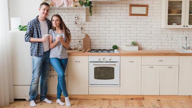 Pareja sonriente en el amor de pie en la cocina Foto gratis
