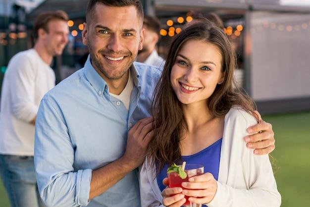 Pareja sonriente en una fiesta en la terraza Foto gratis
