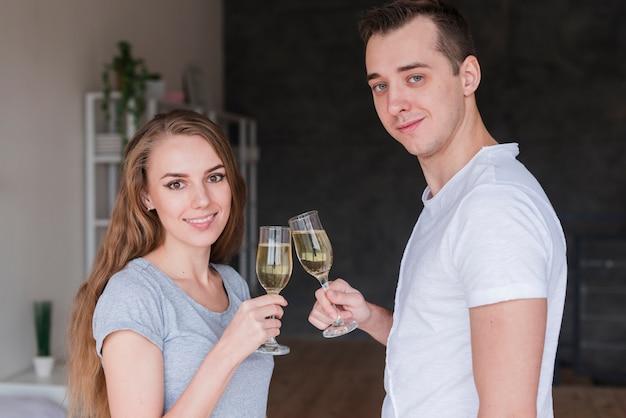 Pareja sonriente joven copas copas de bebida en casa Foto gratis