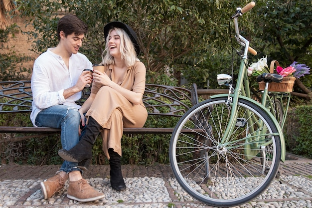 Pareja sonriente en el parque tomando café en el banco Foto gratis