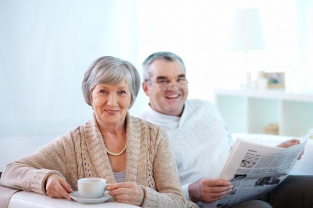 Pareja sonriente tomando café y leyendo el periódico Foto gratis