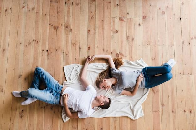 Pareja tendida en el suelo y cogidos de la mano Foto gratis