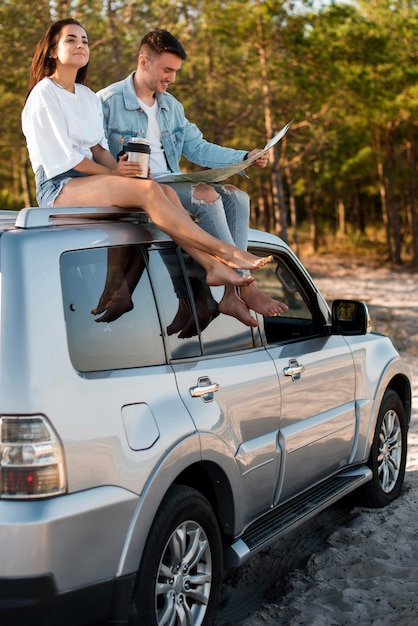 Pareja de tiro completo sentado en el coche Foto gratis