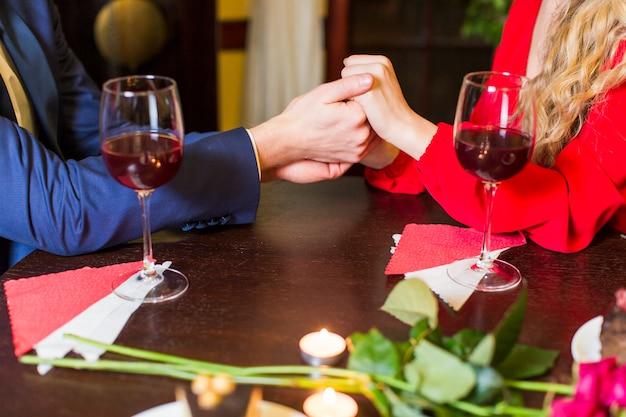 Pareja tomados de la mano en la mesa de madera en el restaurante Foto gratis