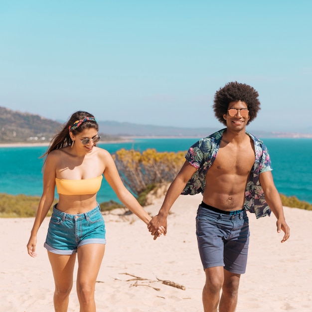 Pareja tomados de la mano de pie en la playa sonriendo y mirando a cámara Foto gratis