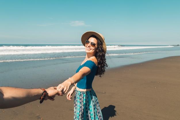 Pareja tomados de la mano de pie en la playa Foto gratis