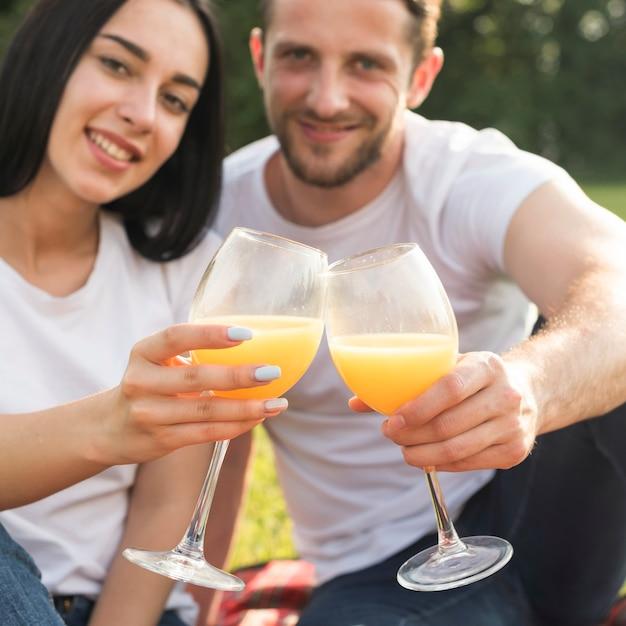Pareja tomando zumo de naranja en manta de picnic Foto gratis
