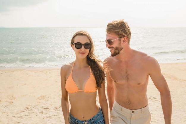 Pareja de turistas jóvenes caminando en la playa en verano Foto Premium