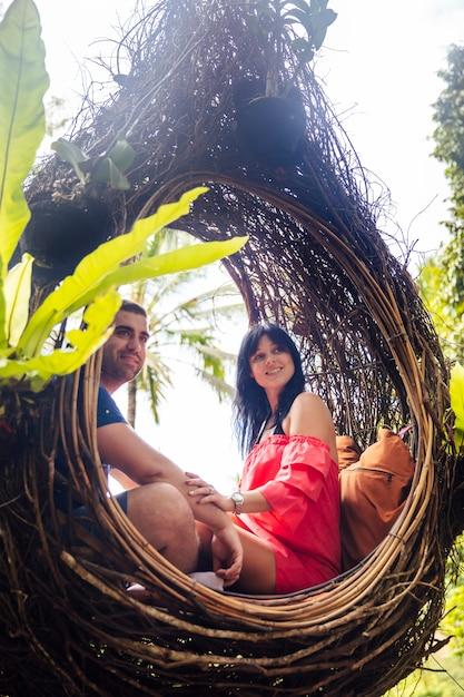 Una pareja de turistas sentados en un gran nido de pájaro en un árbol en la isla de bali Foto Premium