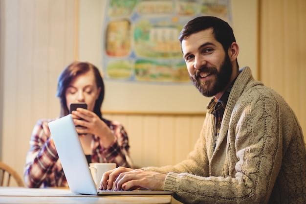 Pareja usando laptop y teléfono móvil Foto gratis