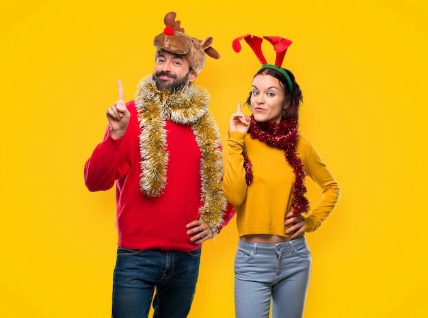 Pareja vestida para las vacaciones navideñas mostrando y levantando un dedo en señal de la b Foto Premium
