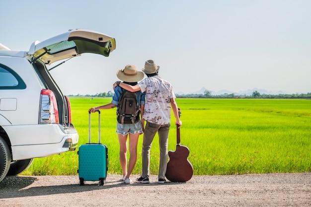 Pareja de viajeros tienen equipaje y guitarra de pie cerca de un coche Foto Premium