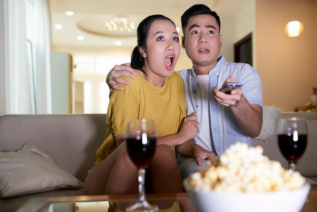 Pareja viendo películas de terror en casa Foto gratis