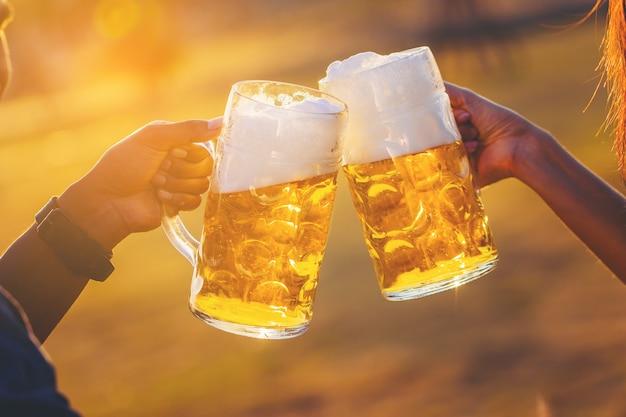Parejas animando cerveza de barril con el sol Foto Premium