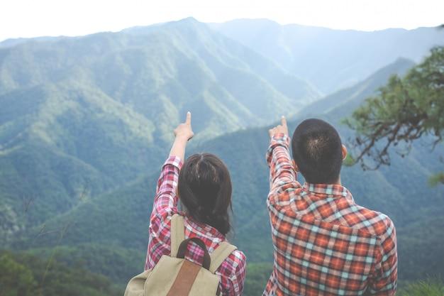 Parejas apuntando a la cima de la colina en el bosque tropical, caminar, viajar, escalar. Foto gratis