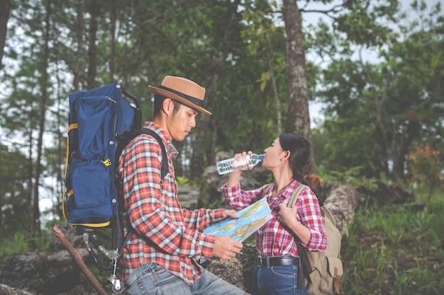 Las parejas beben agua y ven un mapa en el bosque tropical junto con mochilas en el bosque. aventura, viajes, escalada, caminata. Foto gratis