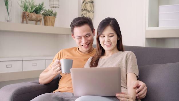 Los pares asiáticos que usan el ordenador portátil y beben la taza de café caliente en la sala de estar en casa, el par dulce goza Foto gratis