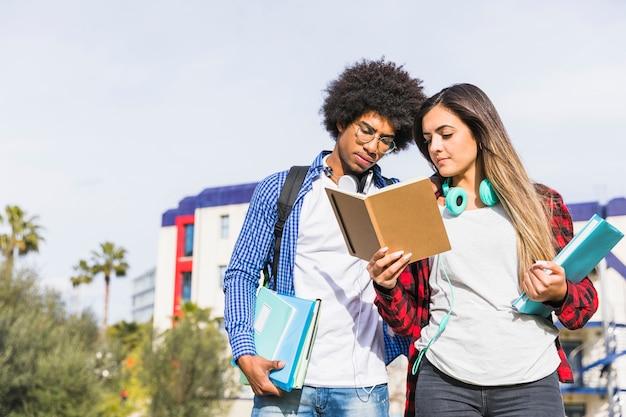 Pares diversos del estudiante que se colocan delante del edificio de la universidad que lee el libro Foto gratis