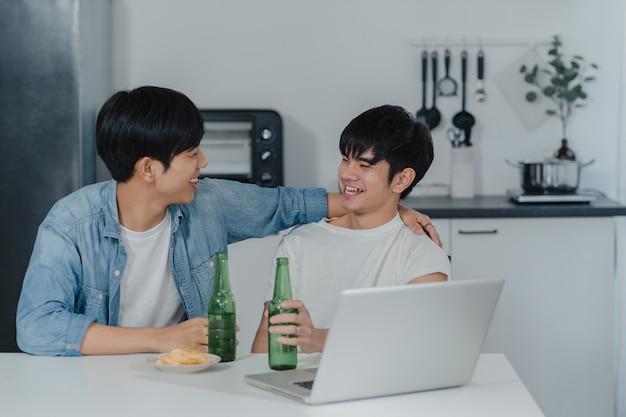 Los pares gay jovenes beben la cerveza mientras que usa la computadora portátil del ordenador en el hogar moderno. los hombres asiáticos lgbtq felices se relajan y se divierten usando la tecnología juegan juntos en las redes sociales mientras se sientan en la cocina de la casa. Foto gratis