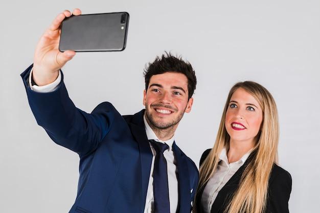 Pares jovenes en el desgaste formal que toma el selfie en smartphone en fondo gris Foto gratis
