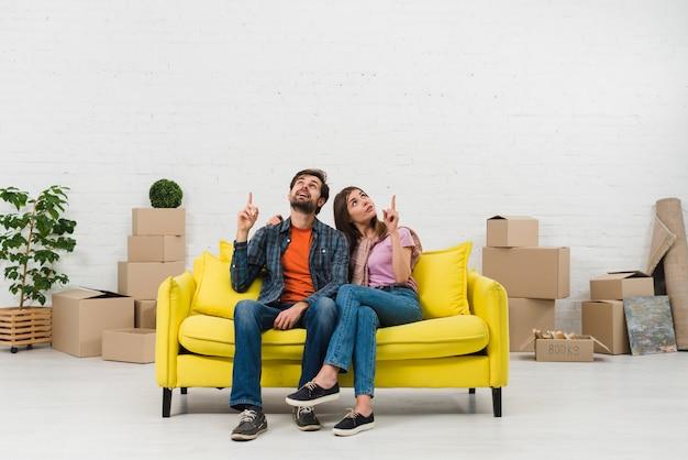 Pares jovenes pensativos que se sientan en el sofá amarillo que señala el finger hacia arriba en nuevo hogar Foto gratis