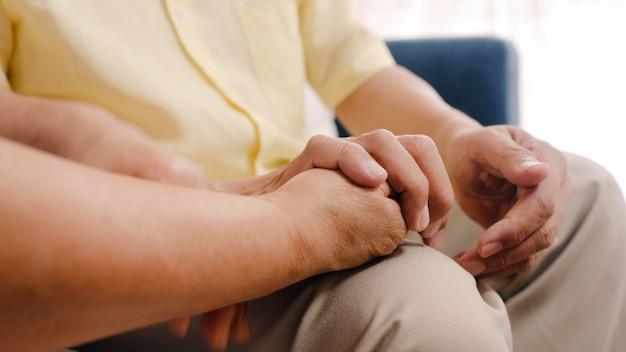 Los pares mayores asiáticos que llevan a cabo sus manos mientras que toman juntos en sala de estar, los pares que sienten parte feliz y se apoyan que mienten en el sofá en casa. Foto gratis
