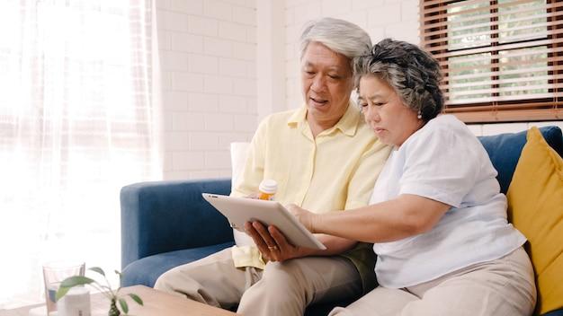 Pares mayores asiáticos que usan la información de la medicina de la búsqueda de la tableta en la sala de estar, pares que usan el tiempo junto mientras que miente en el sofá cuando está relajado en casa. Foto gratis