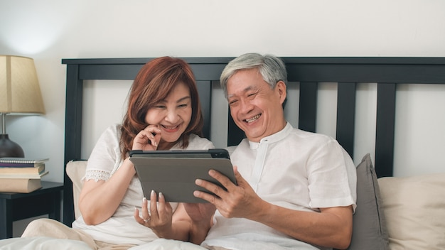 Pares mayores asiáticos que usan la tableta en casa. los abuelos, marido y esposa chinos mayores asiáticos felices después de despertarse, viendo la película acostada en la cama en el dormitorio en casa en el concepto de mañana. Foto gratis
