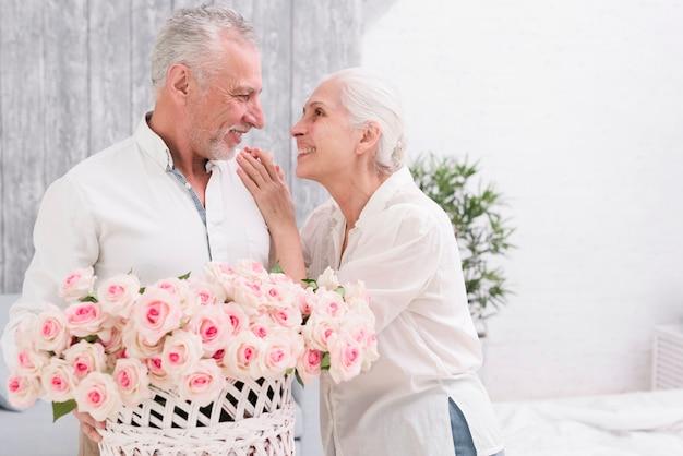 Pares mayores felices que miran el uno al otro que sostiene la cesta de rosas disponibles Foto gratis