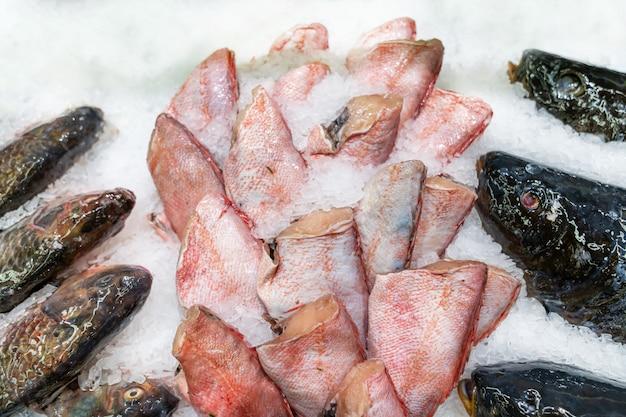 Pargo rojo sin cabeza, pescado fresco en hielo decorado para la venta en el mercado Foto Premium