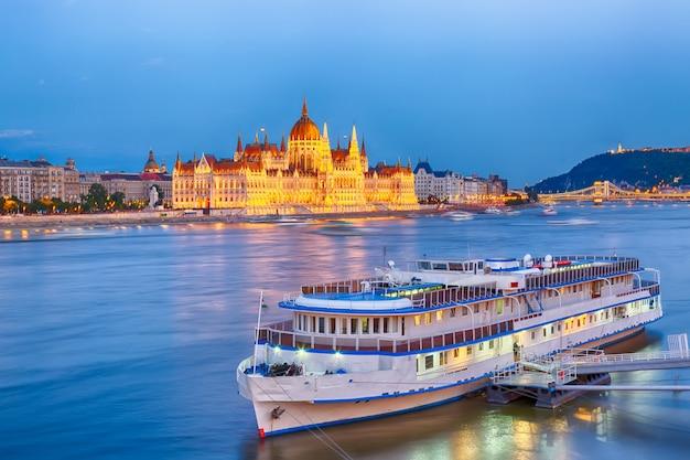 El parlamento y la orilla del río en budapest, hungría, durante la hora azul del atardecer Foto Premium
