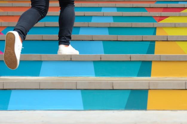 Parte inferior de la adolescente en un zapato informal subiendo una escalera colorida al aire libre Foto Premium