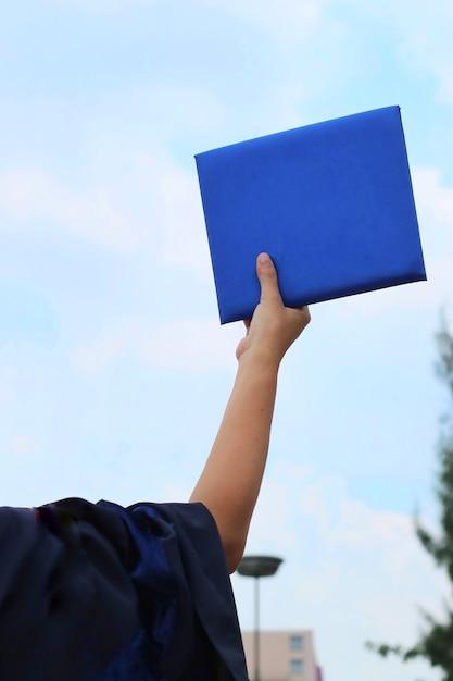 f994c11f4 Parte posterior de la mujer se graduó vestido con certificado de graduación  en la mano Foto