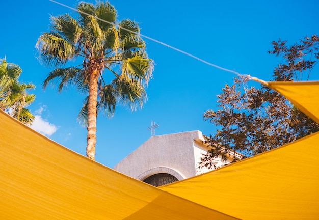 La parte superior de la iglesia a través de decoraciones amarillas de la calle. Foto gratis