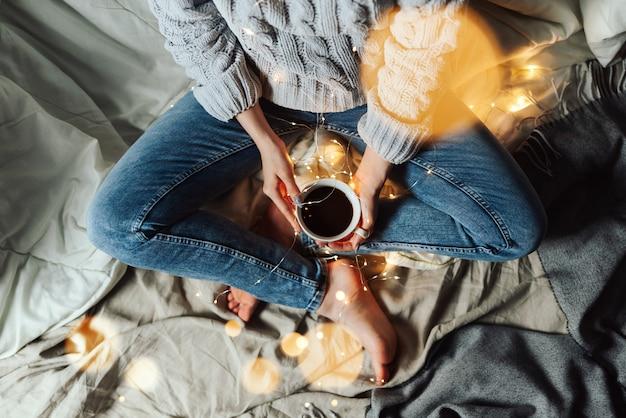 Parte superior de la vista de la mujer sentada en su cama, sosteniendo una taza de café con luces navideñas y bokeh alrededor, enfoque selectivo superficial Foto Premium