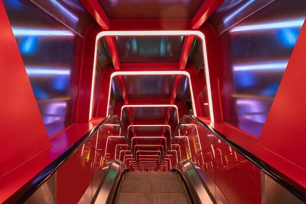 Pasaje circular de escaleras mecánicas con luz roja Foto Premium