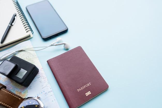 Pasaporte con un mapa sobre fondo azul pastel. planificación de viaje. vista superior de los accesorios de viajero con cámara, ver en el mapa mundial. preparación para el viaje. Foto Premium