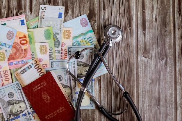Pasaportes húngaros de dinero billetes en dólares estadounidenses y billetes de banco húngaros forints con estetoscopio médico en el hospital del consultorio médico Foto Premium