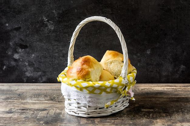 Pascua tradicional hot cross bollos en una cesta en la mesa de madera Foto Premium