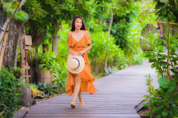 Paseo asiático joven hermoso de la mujer del retrato en paseo del camino en el jardín Foto gratis
