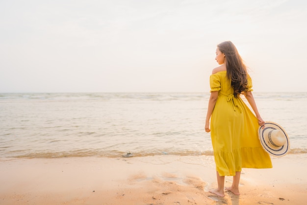El paseo asiático joven hermoso de la mujer del retrato en la playa y el océano del mar con sonrisa feliz se relajan Foto gratis